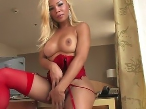 The attractive blonde she-male Karoly Mel in a sexy red lingerie and...
