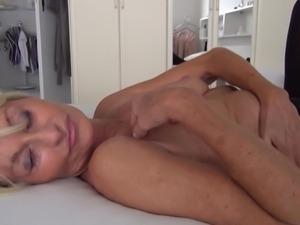 horny mature masturbates on the bed