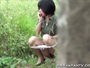 Pissy asian slut plays outdoors