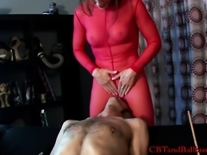 Skinny slave gets his long cock clamped and made to eat a red domme's cunt