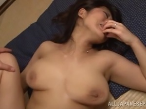 A naturally busty Japanese woman services a lucky dude