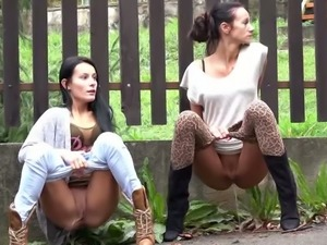 Two kinky chicks flash their nice pussies while pissing near the fence